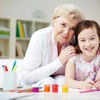 Portrait of happy girl and her grandmother looking at camera at home